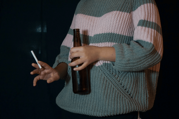 person holding beer and cigarette